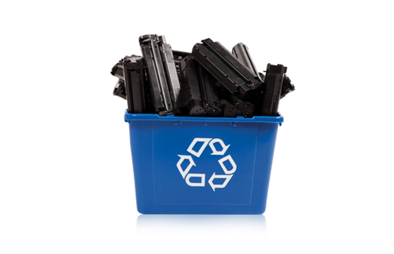 Printer cartridges piled in a blue recycling bin